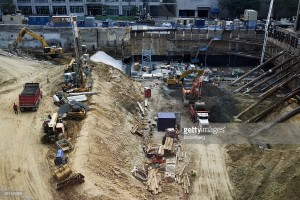 Contractors work at the site of the new Fannie Mae headquarters under construction in Washington, D.C., U.S., on Wednesday, Aug. 17, 2016. The hole at the corner of 15th and L streets, in downtown Washington, is deep -- and getting deeper. Earth-movers there are digging the foundations of a shiny new headquarters for Fannie Mae, the bailed-out giant of American mortgages. Photographer: T.J. Kirkpatrick/Bloomberg